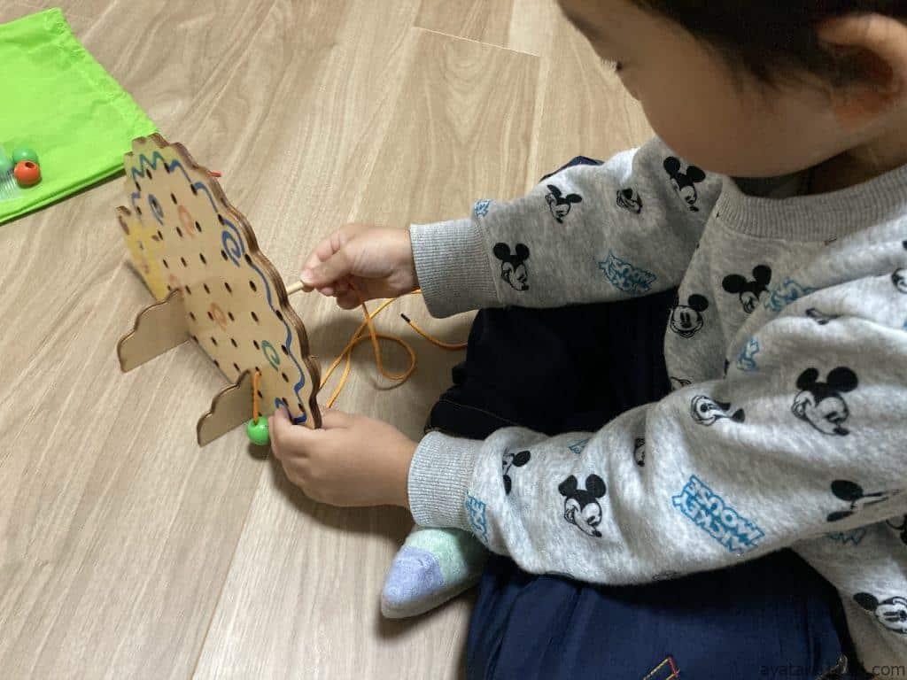 ひもとおしで遊ぶ3歳の息子
